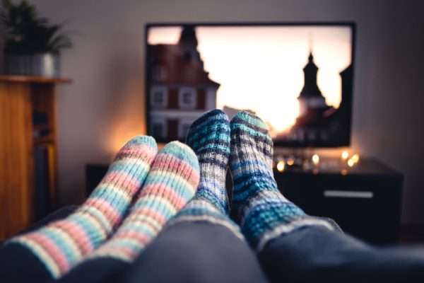 four feet in front of the tv with socks